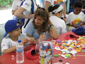 Volunteers help campers decorate sun visors. Perfect for theses sunny days!